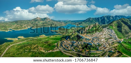 Aerial view of Zahara de la Sierra one of the white towns or Pueblos Blancos, in Andalucia Spain, with a ruined medieval castle and the man made lake formed by the Guadalete river high damn Stockfoto ©