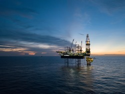 Aerial view offshore drilling rig (jack up rig) at the offshore location during sunset