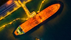 Aerial view oil tanker ship at the port at night, transportation and import export business.
