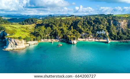 Aerial view on a small beach surrounded by rocks and forest. Coromandel, New Zealand