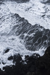 Aerial view on Atlantic ocean in Iceland. Wild waves crushing into the black rocks, view from above