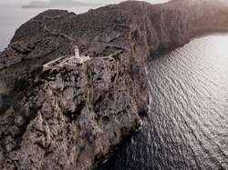 Aerial view on beautiful white Lighthouse of Cap de Formentor in the Coast of North Mallorca, Spain Balearic Islands at sunset. Wide view of wild rocky cliffs. Serpentine Road