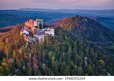 Aerial view on Buchlov Castle, one of the most important castles in Moravia. Monumental castle in Romanesque Gothic style, standing on a wooded hill, lit by reddish light of setting sun. Czech castles Foto d'archivio ©