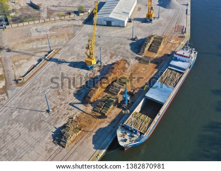 Aerial view on cargo ship in port bank loading wood stack on board using crane.