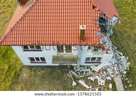 Aerial view on damaged red single house roof after strong wind or explosion. Hole in the rooftop and floor. Rubble on the ground.