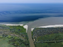 Aerial view on distributary channel Danube river flowing into the Black Sea, Danube Biosphere Reserve in Danube delta. River flowing into the Sea