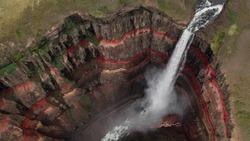 Aerial view on Hengifoss waterfall with red stripes sediments and old soil volcanic formation