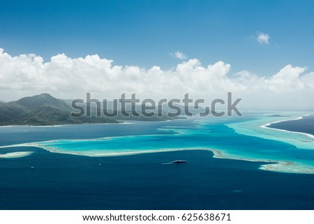 Aerial view on lagoon of Raiatea island in French Polynesia with blue and turquoise water, barrier reef, blue sky, hills with tropical forest and white clouds  #625638671