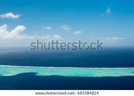 Aerial view on lagoon of Raiatea island in French Polynesia with blue and turquoise water, barrier reef, blue sky and white clouds  #683384824