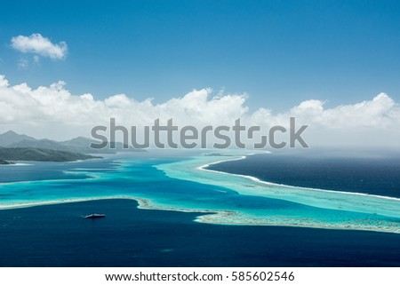 Aerial view on lagoon with blue and turquoise water, barrier reef, blue sky and white clouds of Raiatea island in French Polynesia #585602546