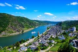 Aerial view on Oberwesel am Rhein. Small town on the upper middle Rhine River, Mittelrhein. Beautiful panoramic Postcard with blue sky, clouds. Rhineland-Palatinate (Rheinland-Pfalz), Germany.  UNESCO