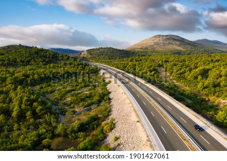 Aerial view on road. Highway through mountain valley. View from a drone. Natural landscape in summer time from air. Travel and vacation. Transportation image Foto stock ©