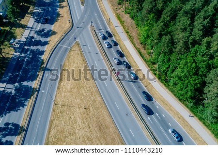 Aerial view on road with cars surrounded with forest  #1110443210