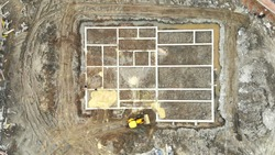 Aerial view on top building foundation. The excavator brings sand for the foundation of the house