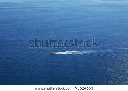 Aerial view on touristic cruise ship sailing on beautiful blue surface of Mediterranean sea in Northern Italy.