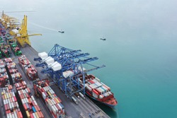 Aerial view over international container cargo ship at industrial import-export port prepare to load containers with big container loader ship vessel. global transportation and logistic business.