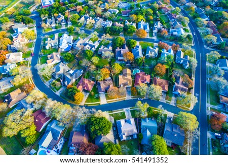 Aerial View Over Modern Suburb Home Community neighborhood with colorful Fall Autumn trees around curved streets and new development outside of Austin , Texas
