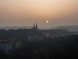 Aerial view over Prague 2 district from Nusle bridge, nuselsky most with typical architecture, old defense wall of Vysehrad castle and Basilica of St. Peter and Paul towers with orange sun in haze