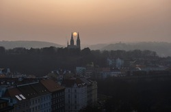 Aerial view over Prague 2 district from Nusle bridge, with typical architecture, old defense wall of Vysehrad castle and Basilica of St. Peter and Paul with orange sun between church towers in haze