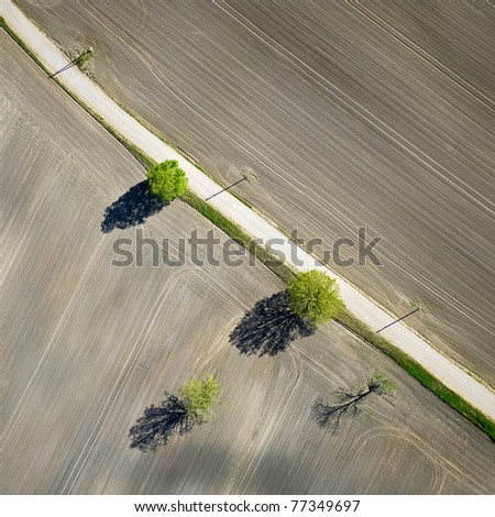 Aerial view over rural field in the late spring - stock photo
