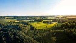 Aerial view over rural landscape in a warm summer sunset tones. Agriculture land mixing with forest and meadows. Green crop fields along the curved river. Trees creating long shadows.