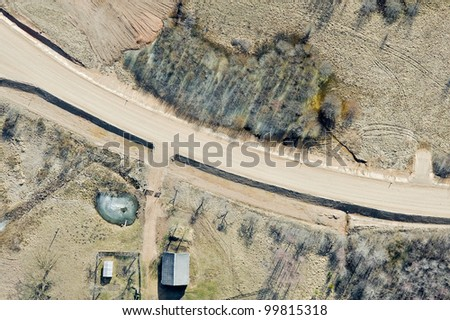 Aerial view over the agricultural fields and country road in springtime