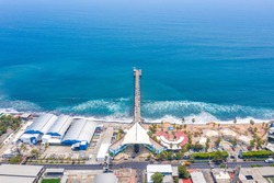 Aerial view over the coastal area on La Libertad beach in El Salvador, where you can see in its entirety its pier and the turquoise sea water.