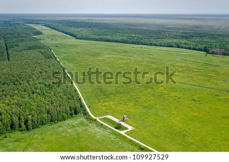 aerial view over the meadows and wild horses and cows - stock photo