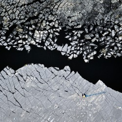 aerial view over the surface of river and cracked ice