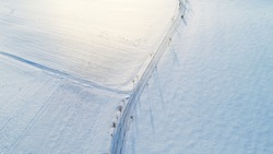 Aerial view over the the snowy field and road. Minimalist landscape concept.