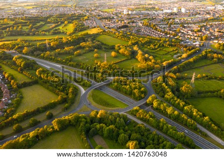 Aerial view overlooking a typical British highway intersection. Stunning sunset light gives the nearby trees, fields and houses that gorgeous golden glow. #1420763048