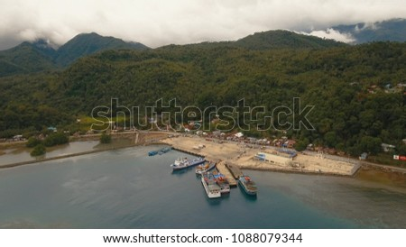 Aerial view:passenger ferry terminal with ferry boats.Ferries for transport vehicles and passengers in the port.Sea passenger port on a tropical island.Philippines, Camiguin. Travel concept.