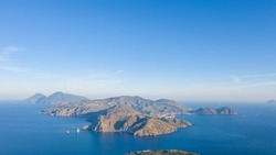 Aerial view photo from flying drone of Panoramic view from the volcano of Vulcano Island in a summer day. The islands of Lipari and Salina are visible in the distance, Aeolian Islands, Sicily, Italy.