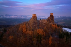 Aerial view, picturesque ruins of gothic castle Trosky in UNESCO national park Czech Paradise (Cesky raj) during colorful sunset. Towers of medieval monument in winter Czech landscape. Czech Republic.