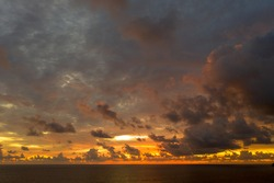 aerial view rain clouds Dark storm clouds over ocean open sea in evening sky sunset.stunning red sunset landscape Amazing light of nature cloudscape sky in twilight.