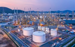 Aerial view Refinery and oil storage tanks at dusk and night. Petrochemical and energy oil industries.