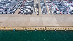 Aerial view row of new cars parked at commercial port for import and export business logistic to dealership for sale, Automobile and automotive car parking lot for commercial global business industry.