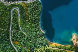 Aerial view serpentine road and forest with sea drone landscape in Norway above trees and blue sea water scandinavian nature wilderness top down scenery