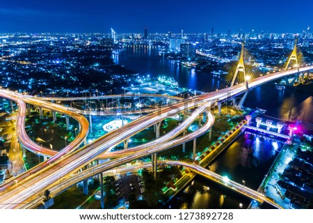 Aerial view shot or intersection of highway road with cityscape background for transportation or traffic. #1273892728