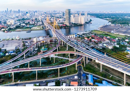 Aerial view shot or intersection of highway road with cityscape background for transportation or traffic. #1273911709