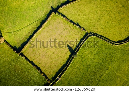 Aerial view showing geometric lines and shapes made by field boundaries in British countryside.