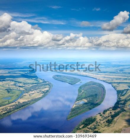 Aerial view the great river during summer day on background of  white clouds which reflect in water.