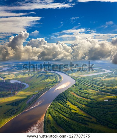 Aerial view the river during summer day under the great clouds.