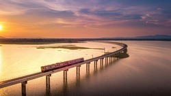 Aerial View The train is running on the bridge Over River Pa Sak Dam Lopburi Thailand and Beautiful sunset