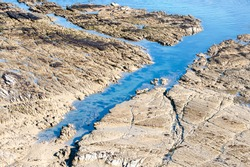 Aerial view to exposed rocks along shoreline. Turquoise sea contrasts with sandy coloured limestone shelf