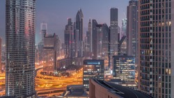 Aerial view to financial district with new towers and tall buildings with busy roads night to day transition timelapse in Dubai Downtown from above with traffic on highway, Dubai, United Arab Emirates