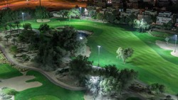 Aerial view to Golf course and villas with houses night timelapse. Illuminated lawn. Lakes with fountains