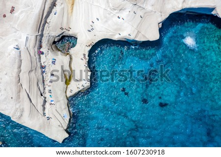 Aerial view to the chalk rock formations of Sarakiniko with people enjoying the sparkling blue sea on a hot summer day, Milos island, Cyclades, Greece Foto d'archivio ©