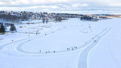 Aerial view to the frozen ice surface of the Lake Viljandi with the skating paths and distant unknown skaters on training