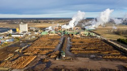 Aerial view to the modern industrial sawmill with the numerous piles of timber waiting to be processed